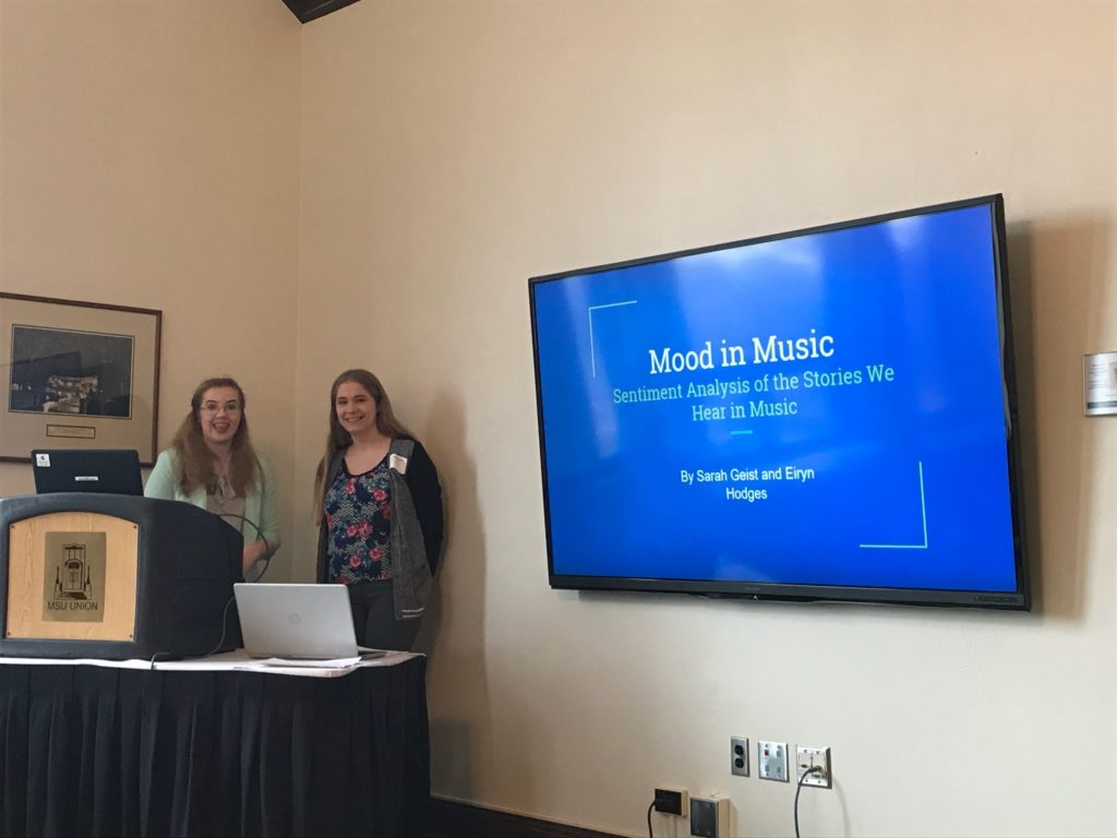 """Two women smile in front of a large screen that reads, """"Mood in Music."""""""